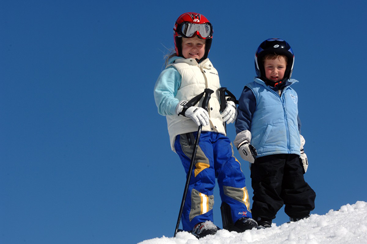 A girl and a boy in winter clothes and helmets, standing at the top of a ski slope.