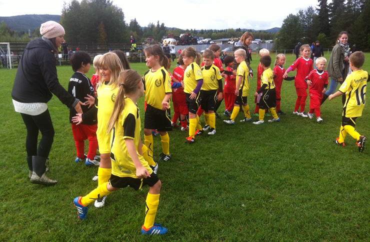 Young children wearing yellow or red football jerseys thank each other after a match.