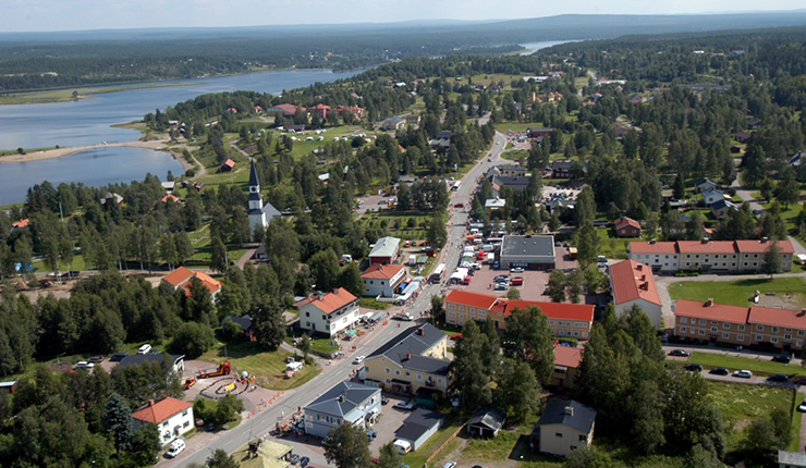 Aerial photo of Särna, with residential houses and shops. The church is just left of centre, and Särnsjön furthest to the left.