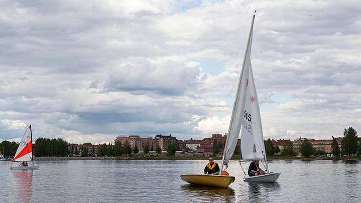 Three sailing dinghies on the lake, with Ludvika in the background.