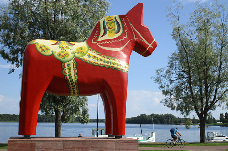 A red Dala horse, several metres tall, standing outside and with water in the background.