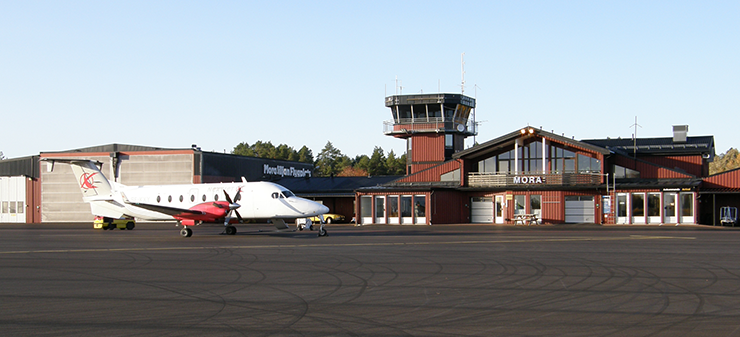 Mora/Siljan Airport, with a twin-engine airplane in the foreground and a hangar and terminal in the background.