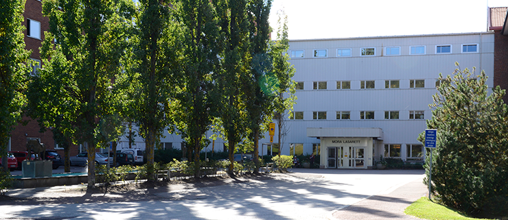 The entrance to Mora Hospital. The building is white and has four floors. There are leafy trees in the foreground.