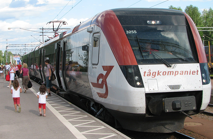 Tågkompaniet's train by the platform, with children and adults in summer clothes getting off and on.