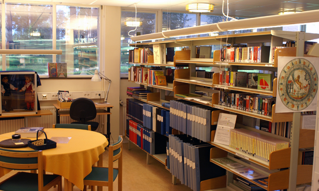 A library with bookshelves, a study corner and a round table with a few chairs.