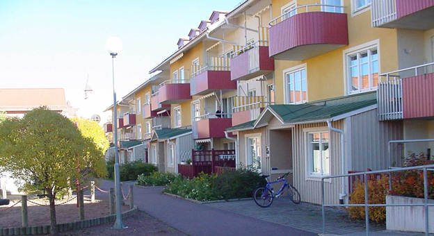 A row of yellow, three-storey blocks of flats with red balconies, with a playground just visible on the left.
