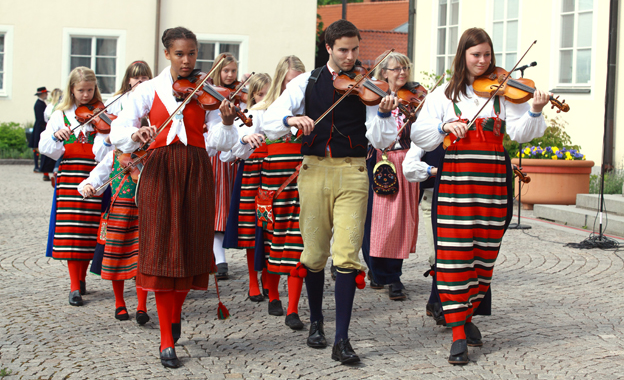 Young folk musicians, men and women, walking in single file. They are playing fiddles and wearing regional folk costumes.
