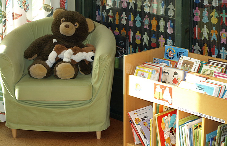 Reading corner for the youngest at the library. Books for small children in a box, and a green armchair with cuddly soft toys.