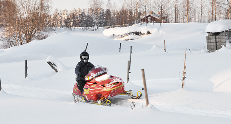 A winter day with fresh snow. At the centre of the image is a person wearing winter clothes, ski goggles and a helmet and sitting on an orange snowmobile.