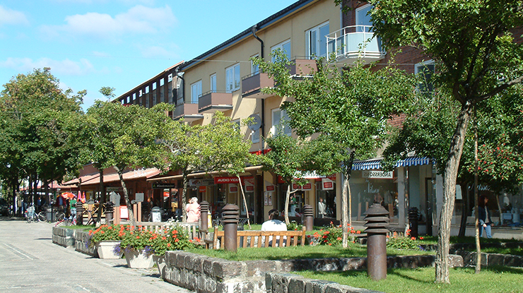 A street with low buildings of rented flats with shops on the ground floor. Outside the shops are seating areas surrounded by patches of grass and trees.