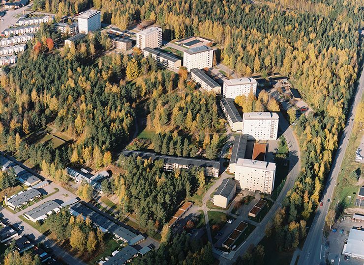 Aerial photo of a residential area with different types of blocks of flats and parking lots. The surroundings are dominated by spruce forests.