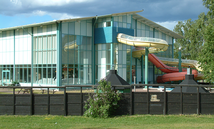 The exterior of Parkbadet. Covered water slides snake their way from the building's façade, and outside it are seating areas.