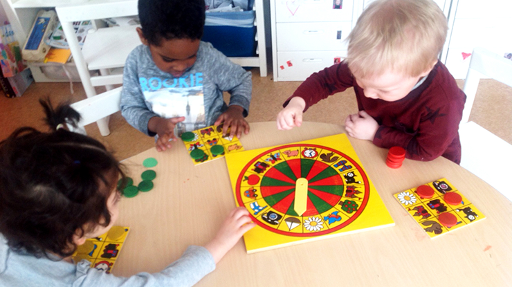 Three preschool-age children seated around a table, playing a board game.