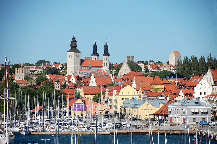Sailing boat masts in the foreground in Visby harbour, with Visby buildings in the background.