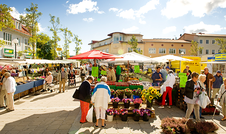 The market in Kungsbacka's central square on a spring day. Two elderly women in the foreground admire the flowers in one of the stalls.
