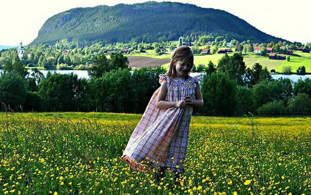 A girl in a meadow of yellow flowers. In the background are a stream, residential houses, farms, and a big mountain in the distance.