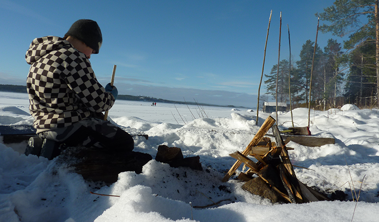 A teenage boy seated by a campfire on a winter day, whittling a piece of wood. In the background are two people walking across snow-covered ice on a lake.