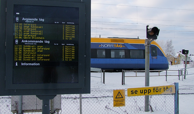 A Norrtåg train at the station. In the foreground is an information board showing departures and arrivals.