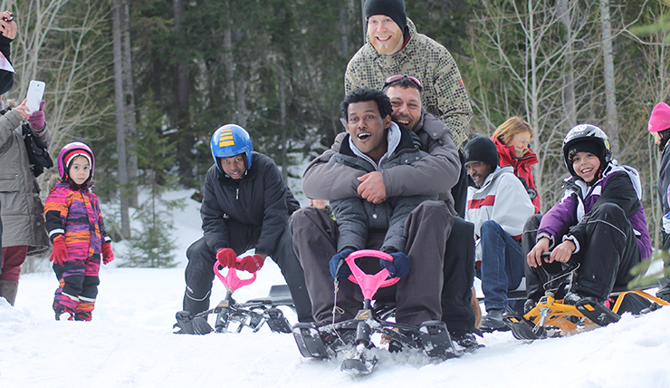 Adults and children playing in the snow. Several people are descending a slope on snow racer sleds.
