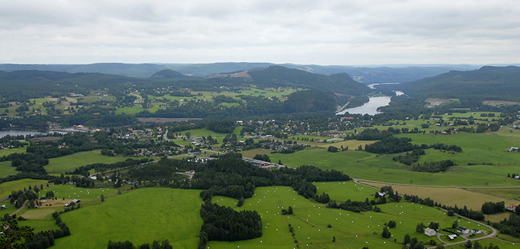 Aerial photo of the Ragunda Valley with scattered houses, meadows, and the Indal River and mountains in the background.