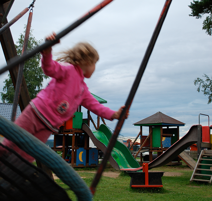 A playground with slides, a climbing frame and swings. A girl dressed in pink is swinging standing up on a big round swing.