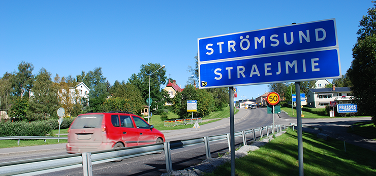 A red car on its way into Strömsund, passing a sign with the town's Swedish name and its Sami name, Straejmie.