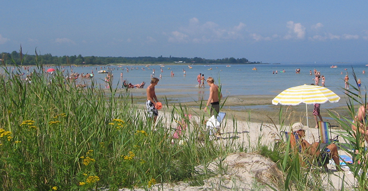 Long sandy beach with tourists and locals swimming, in warm summer weather.