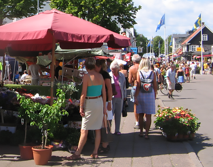 A street full of market stalls, with lots of people in summer clothes moving between them.