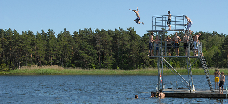 A beach where large numbers of young people are swimming and diving into the water from a diving tower on a warm summer day.