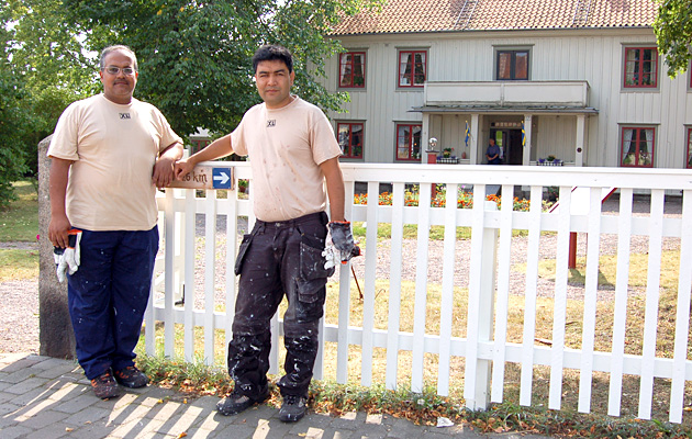 Two workmen lean against a fence outside a property, with a white wooden house in the background.