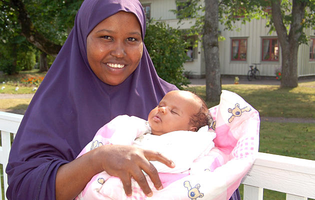 A young mother wearing a mauve veil, with her sleeping baby in her arms.