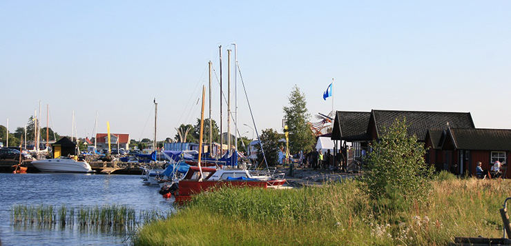 Pleasure craft, both sailboats and motorboats, moored in a natural harbour. A few houses and the harbour master's office can also be seen.