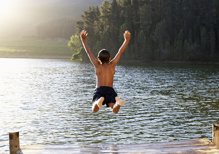 A boy dives into a lake from a jetty. It is summer and the weather is sunny.