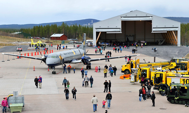 Gällivare airport. A propeller airplane is parked on the ground. Several yellow lorries are also parked at the airport. People are walking around looking at the airplane and the vehicles.