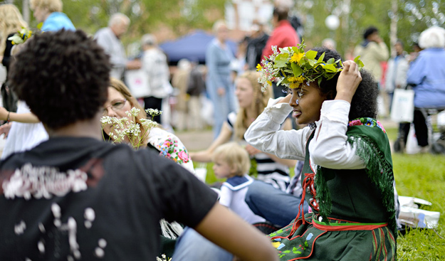 Midsummer festivities. A girl is sitting on the grass. She is wearing a folk costume and has a garland of midsummer flowers in her hair.