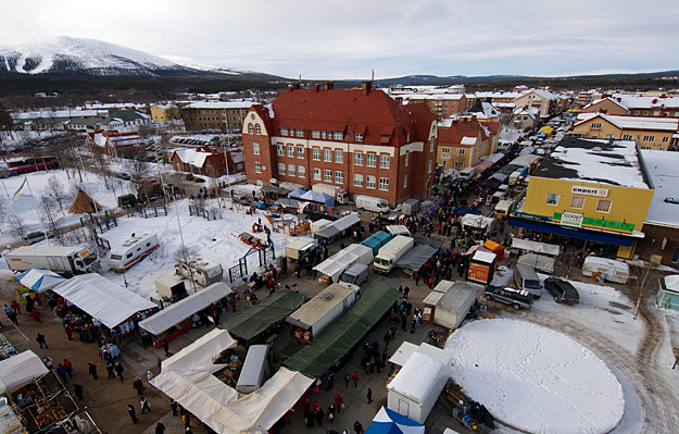 Gällivare winter market seen from the air. Various tents have been pitched along a wide street. There are crowds of people at the market.