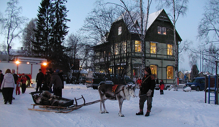 A man is leading a reindeer pulling a sled. It is winter, and there is snow on the ground.