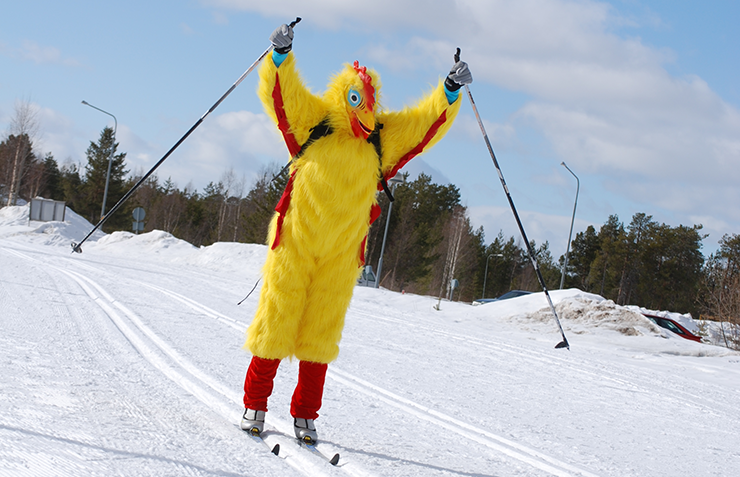 A person is cross-country skiing outdoors. The person is dressed up as a yellow chicken.
