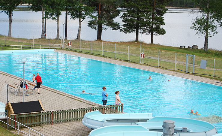Four people are swimming in an outdoor pool. Two people are standing next to the pool, watching. There is a water slide at one corner of the pool.