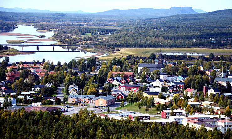 View of the built-up area of Överkalix, with mountains in the background. The area is surrounded by forest and lies next to a river.