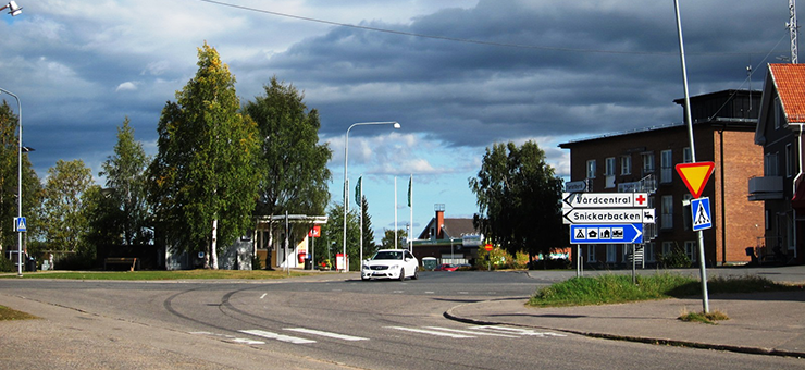 The centre of Pajala. A white car is driving along the road. In the background is a brick house.