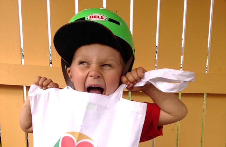A child wearing a cycle helmet is holding a cloth bag and smiling broadly.