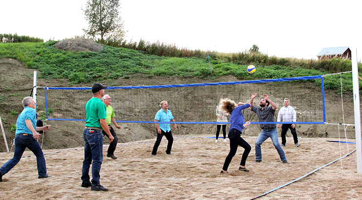 A group of people are playing beach volleyball.