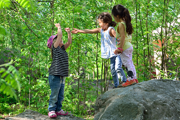 Three preschool children playing in a wood.