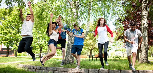 Young people in a park leaping from a wall.