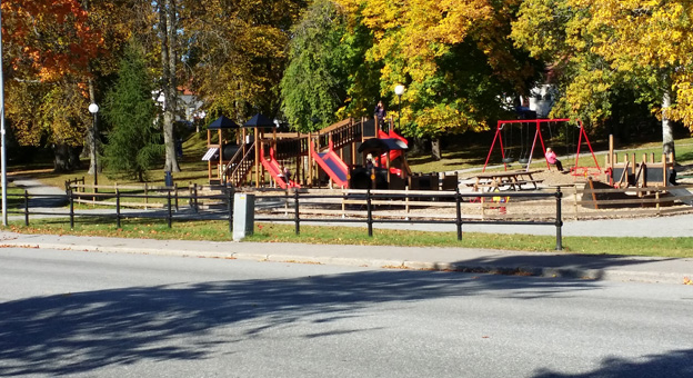A park with a playground. There are slides and swings in the playground.