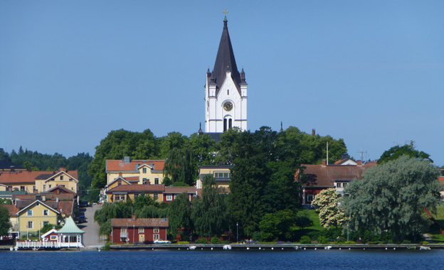 View of the community of Nora. In the foreground is a lake. A white church with a black roof towers on the horizon.