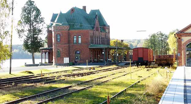 The railway station in Nora. The station building, in the background, is a red brick building with a green tin roof.