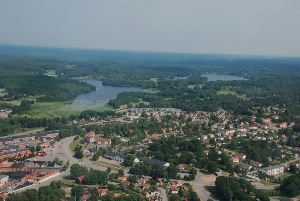Aerial view of the community of Åtvidaberg. A lake and a forest can be seen in the distance.