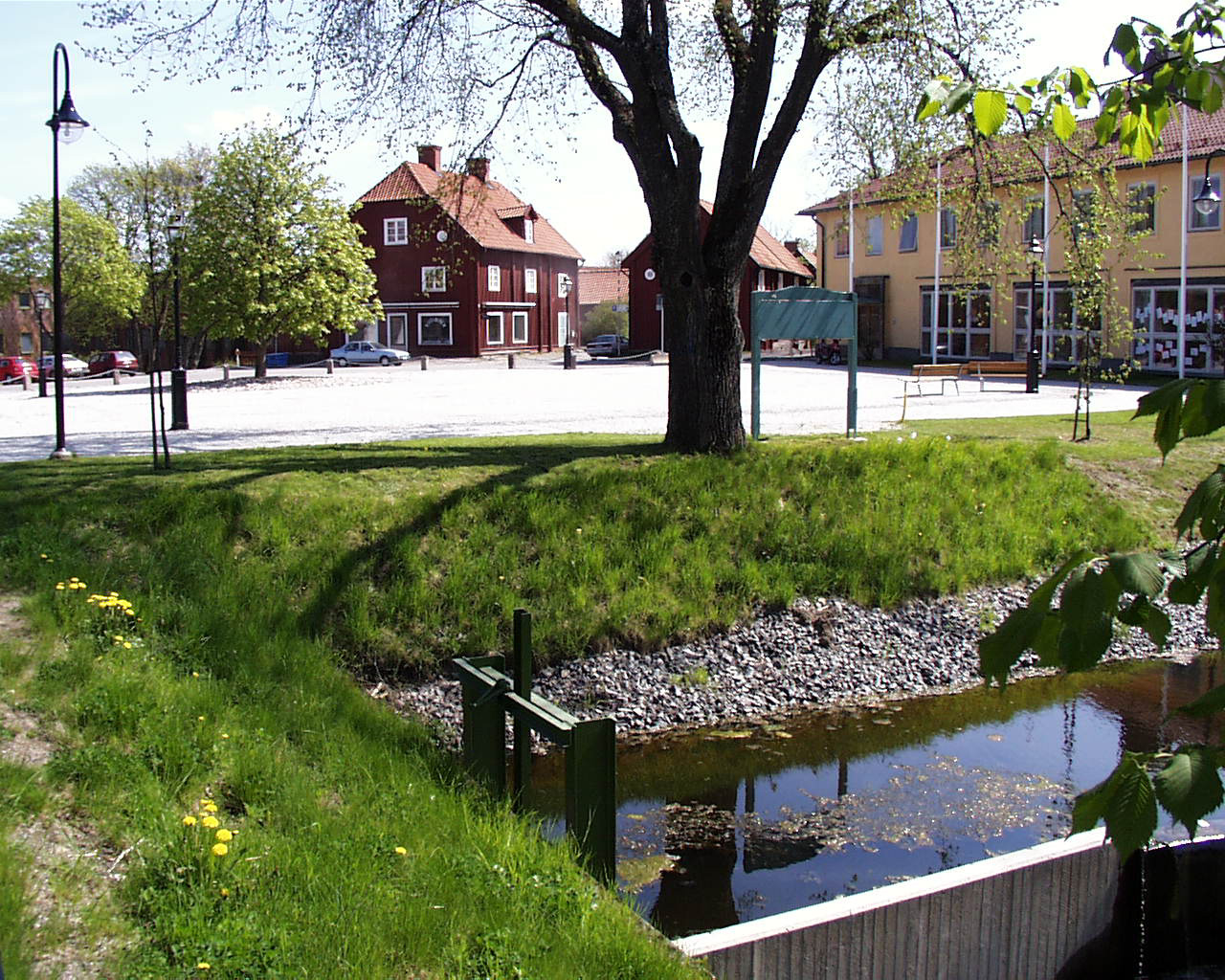 A square in Åtvidaberg. In the background cars are parked next to an old building. In the foreground is a pond.